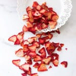 ried strawberries being poured from a plate onto a counter.
