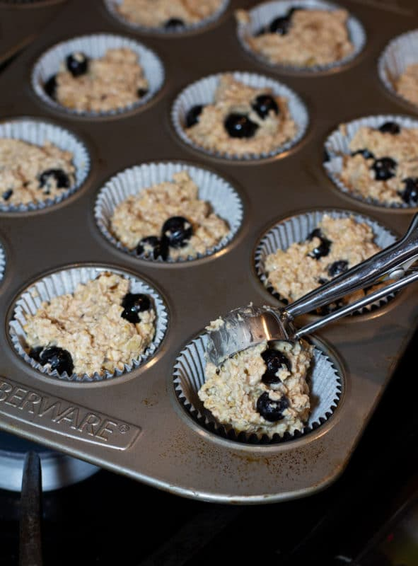 Person using a scoop to add oatmeal mixture to muffin cups.
