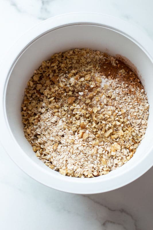 White bowl filled with dry ingredients for making banana oatmeal muffins.