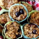Banana muffins in a wooden bowl topped with blueberries.