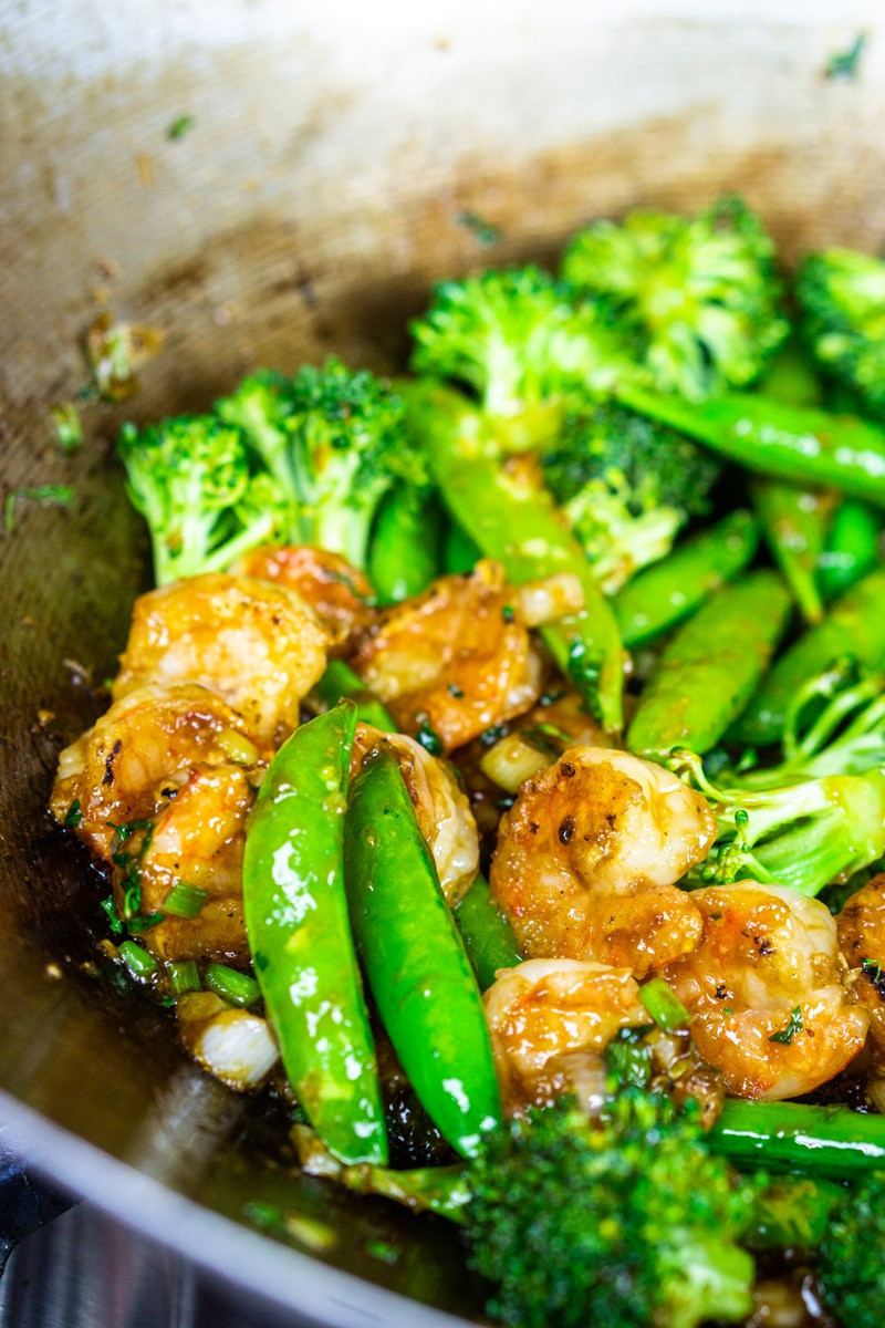 Shrimp stir fry in a skillet with broccoli and sugar snap peas.
