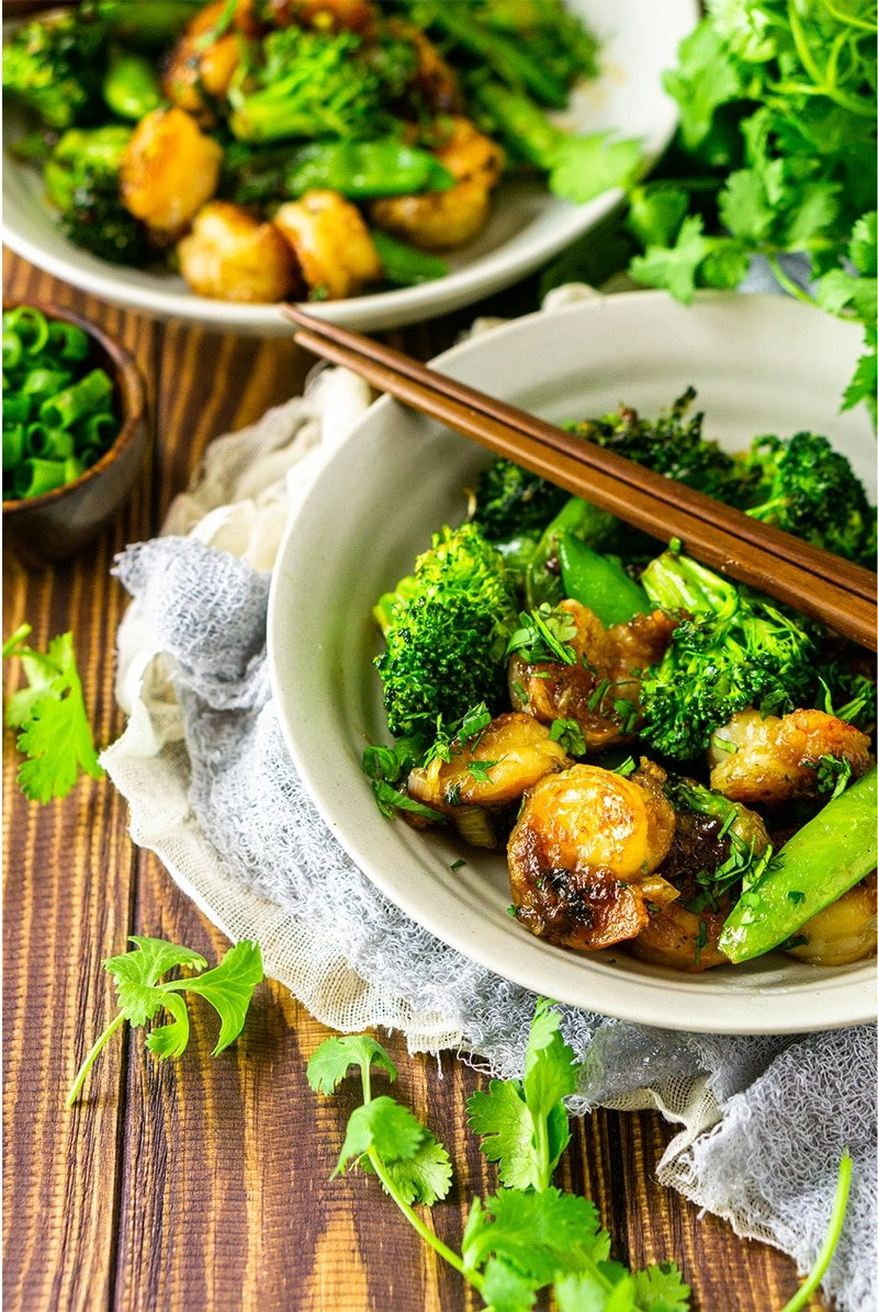 Bowl containing sauteed shrimp with stir fry vegetables.