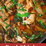 Sauteed chicken breasts in a skillet topped with cooke peaches, tomatoes, and fresh basil.