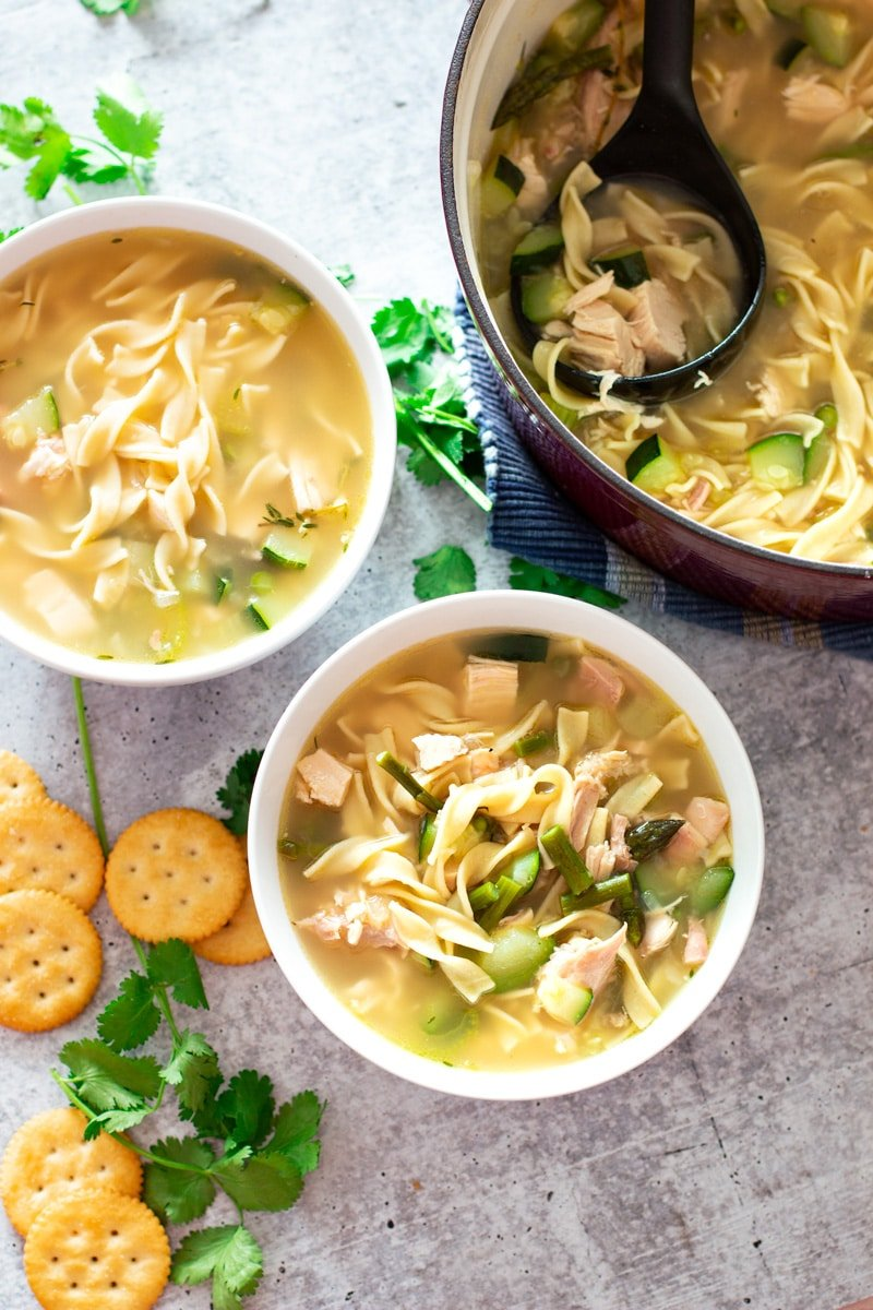 Ladle in a stockpot of soup, white bowl on a table containing chicken noodle soup with vegetables.
