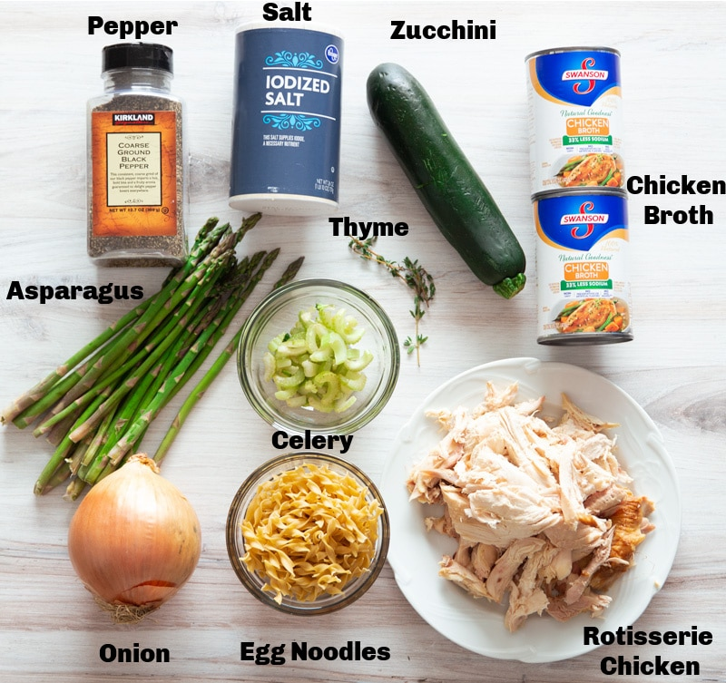 Salt, pepper, rotisserie chicken, egg noodles, onion, asparagus, thyme, and chicken broth on a table.