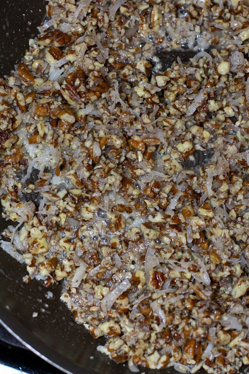 Close up of toasted pecans and coconut in a skillet.