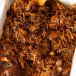 Slow cooker pulled pork in a glass dish.