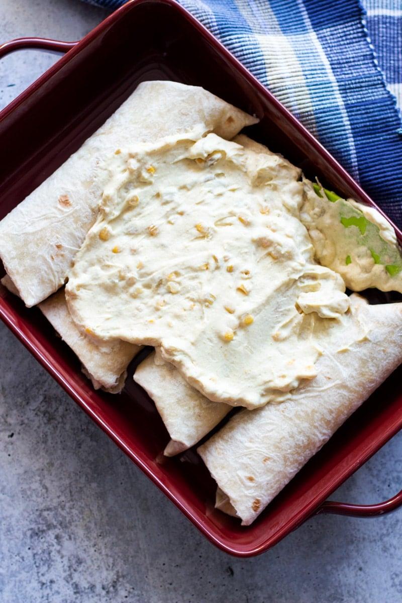 Creamy enchilada sauce on top of 4 chicken enchiladas.