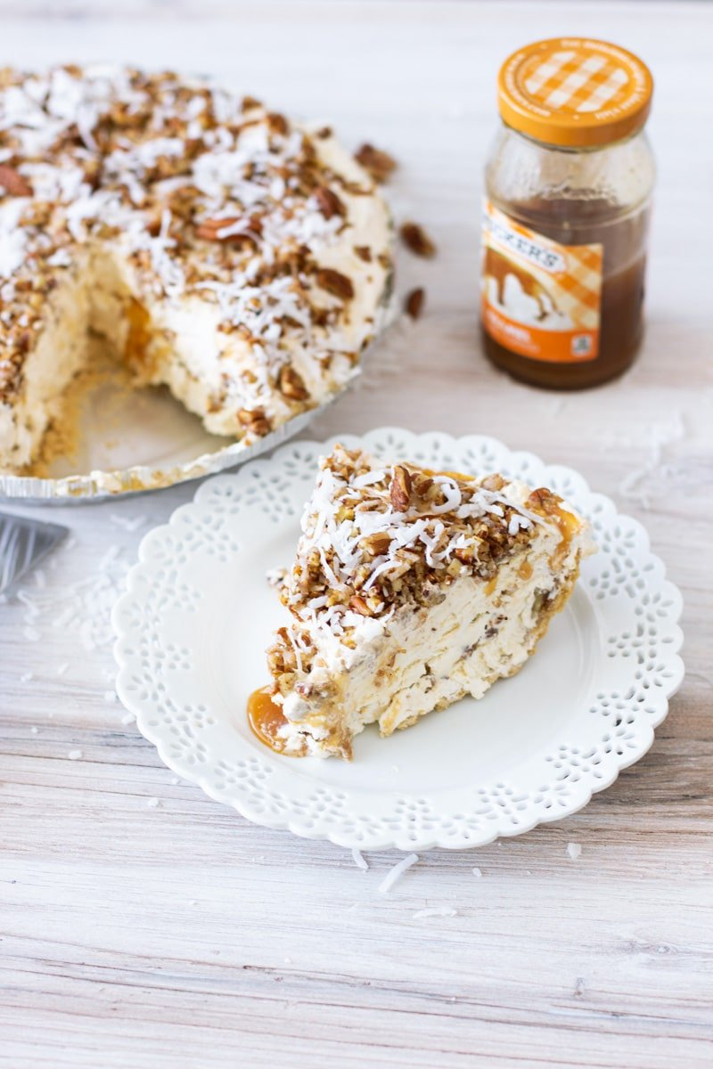 Slice of frozen pecan pie on a plate, caramel topping on counter.