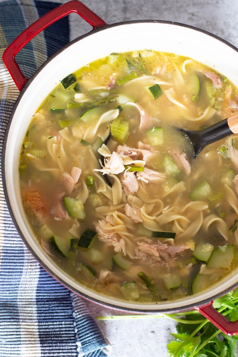 Ladle in a stockpot filled with vegetables, noodles, and chicken broth.