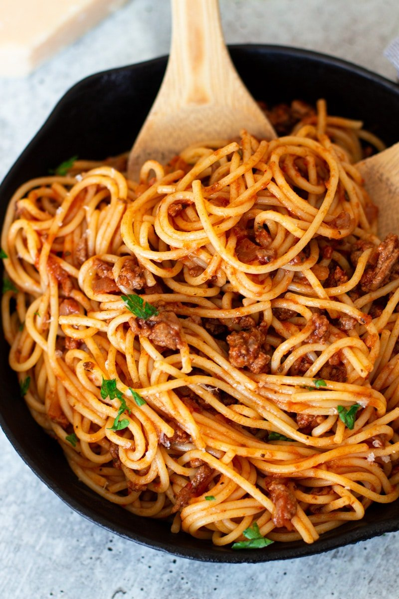 Pan containing spaghetti and meat sauce, serving spoons in pan.