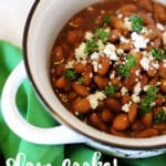 Bowl of slow cooked pinto beans topped with feta cheese.
