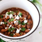 Pinto beans made in a crockpot topped with feta cheese and parsely.