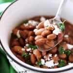 Bowl of pinto beans, spoonful of beans with cheese and parsley.