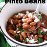 Spoonful of pinto beans topped with parsley and cheese.