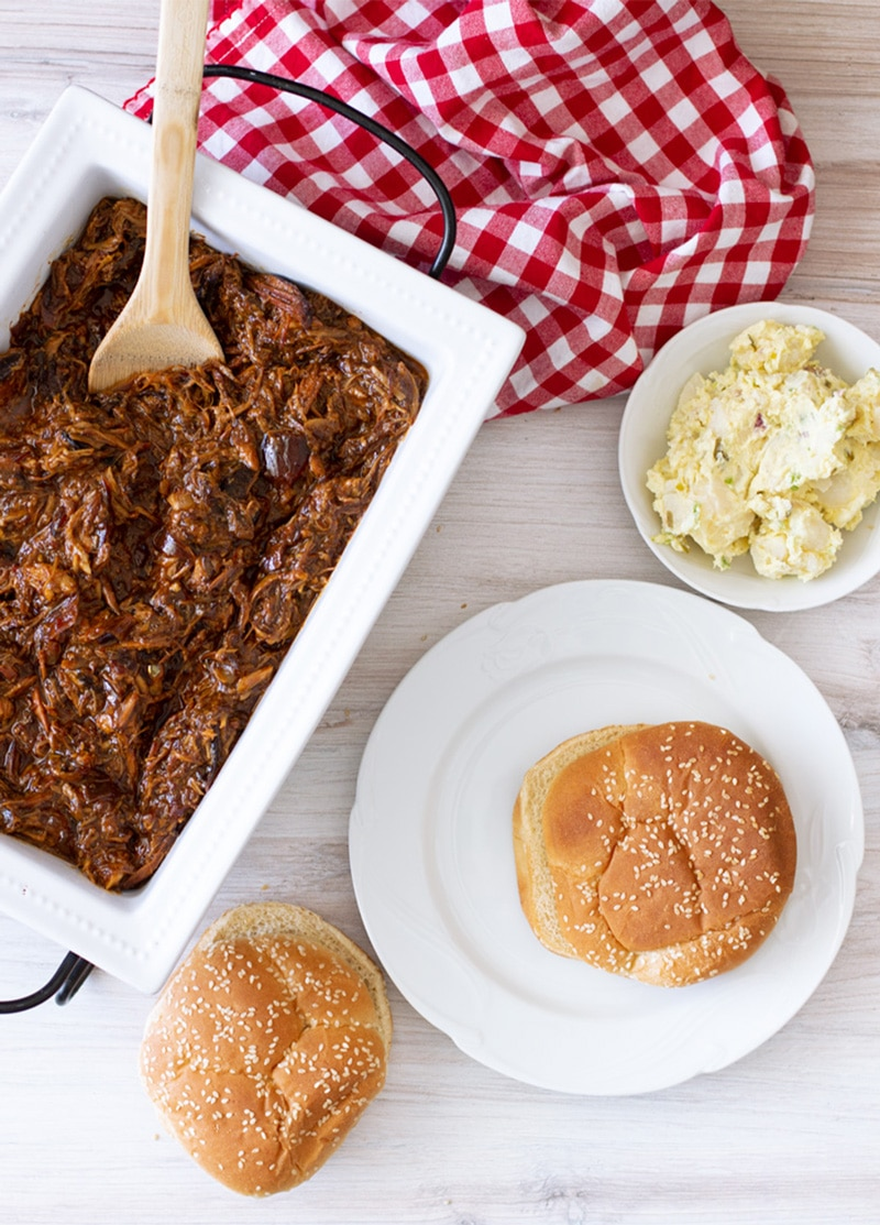 Bun on a plate, slow cooker pulled pork in serving dish.