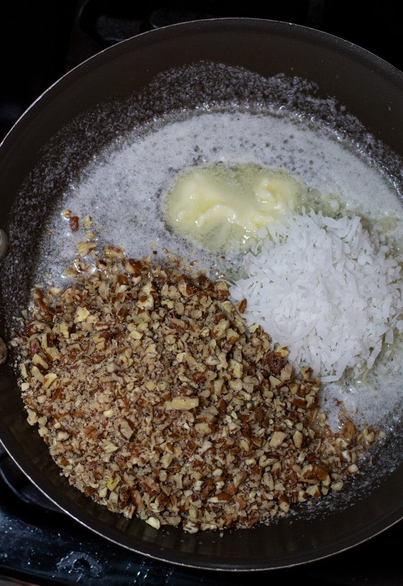 Skillet on a stovetop containing pecan chips, melted butter and shredded coconut.