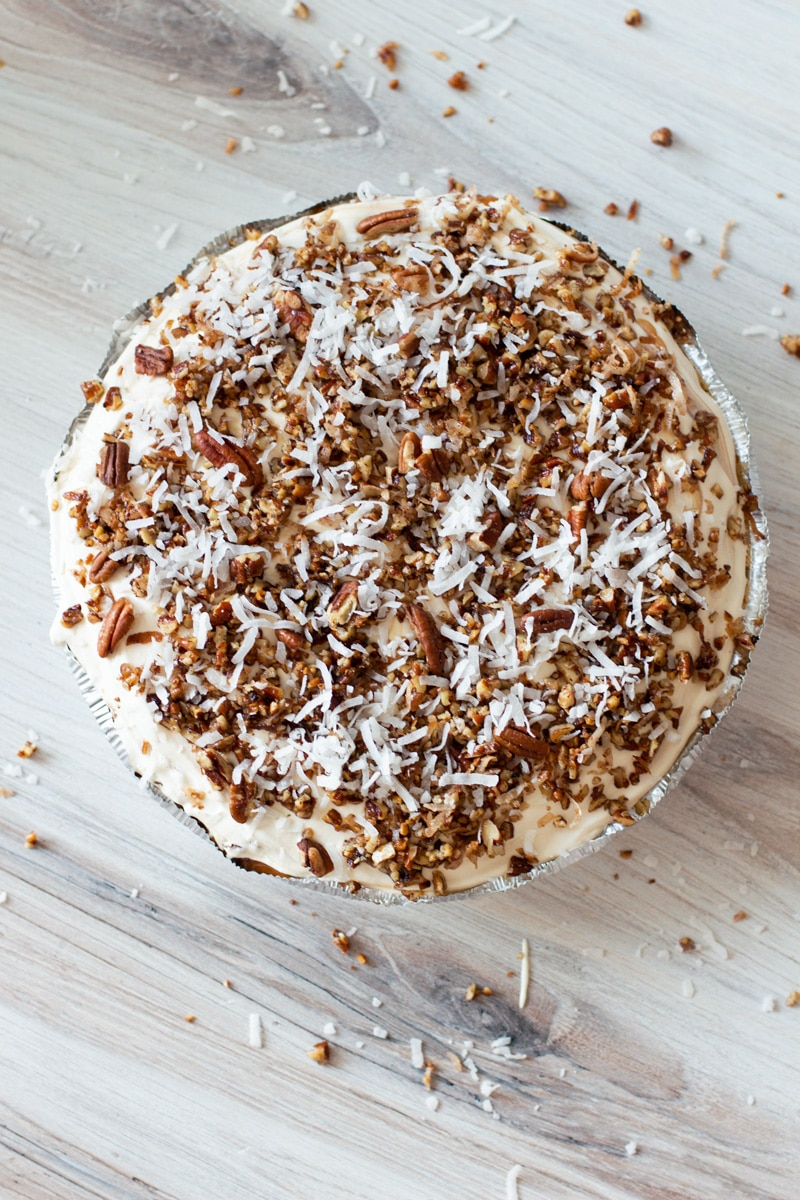 No bake frozen pecan pie on a counter, topped with pecan chips, caramel, and toasted coconut.