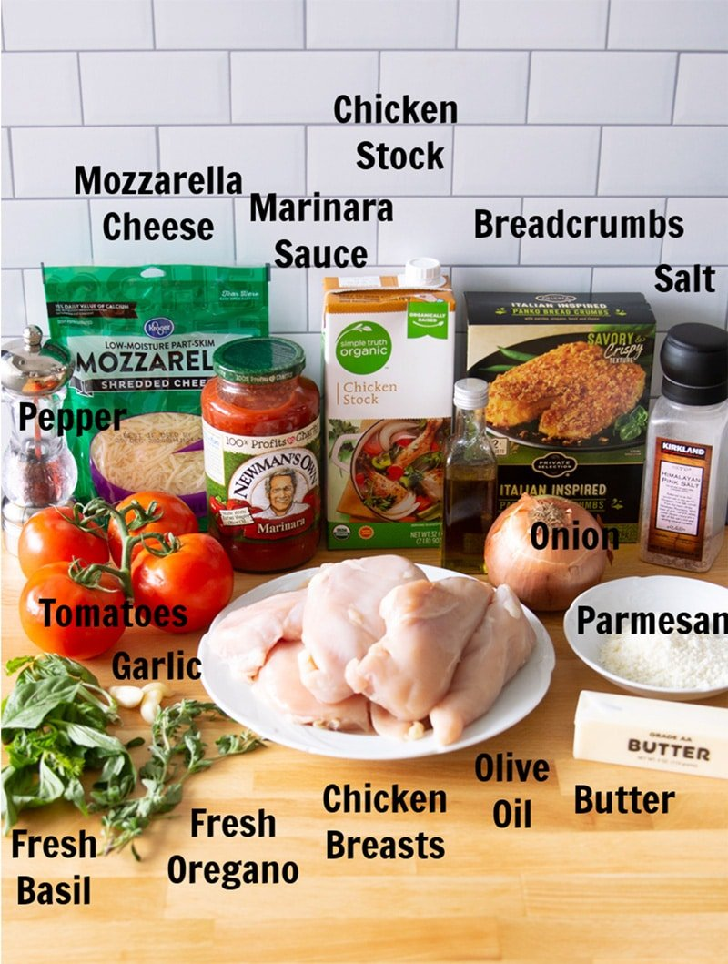 Chicken, cheese, tomatoes, chicken stock, breadcrumbs, and other ingredients on a counter to make chicken parmesan.
