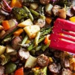 Sheet pan dinner containing smoked sausage, potatoes, peppers, asparagus, and broccoli.