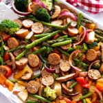 Sheet pan dinner filled with red onions, broccoli, smoked sausage, peppers, and peppers.
