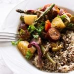 Smoked sausage and vegetables served over a bowl of quinoa.