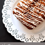 Zucchini bread loaf on a white plate topped with a cream cheese glaze.