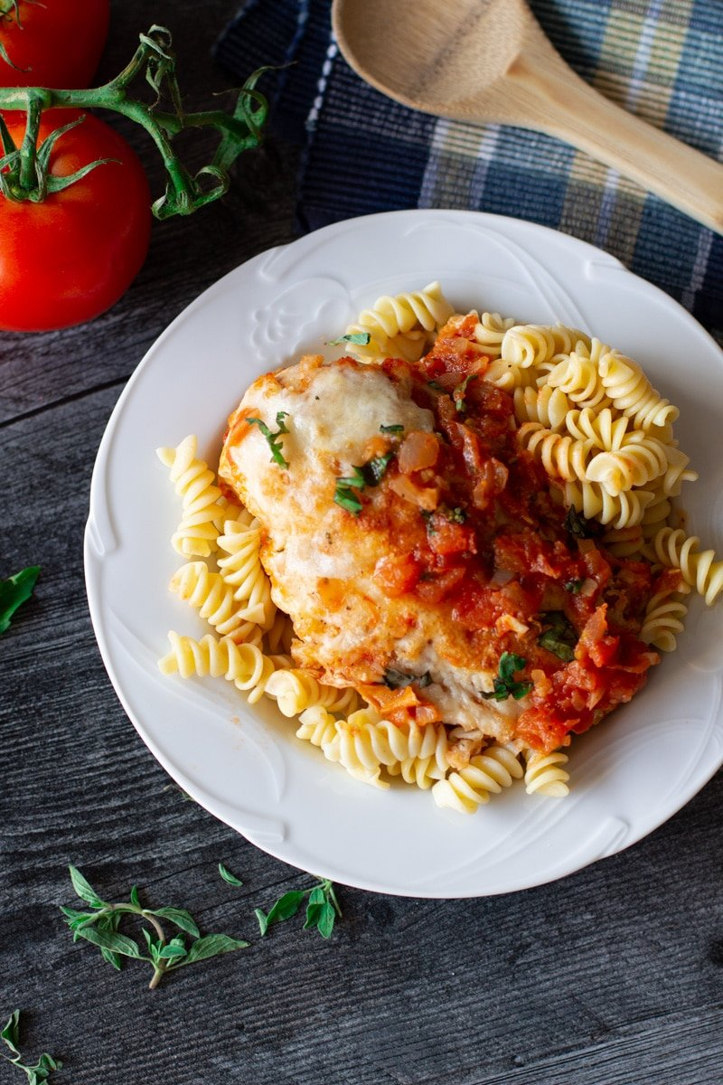White plate containing chicken parmesan sitting on a bed of rotini noodles.