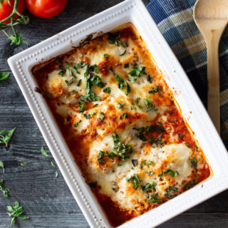 White dish containing baked crusted chicken parmesan topped with melted cheese and fresh basil.