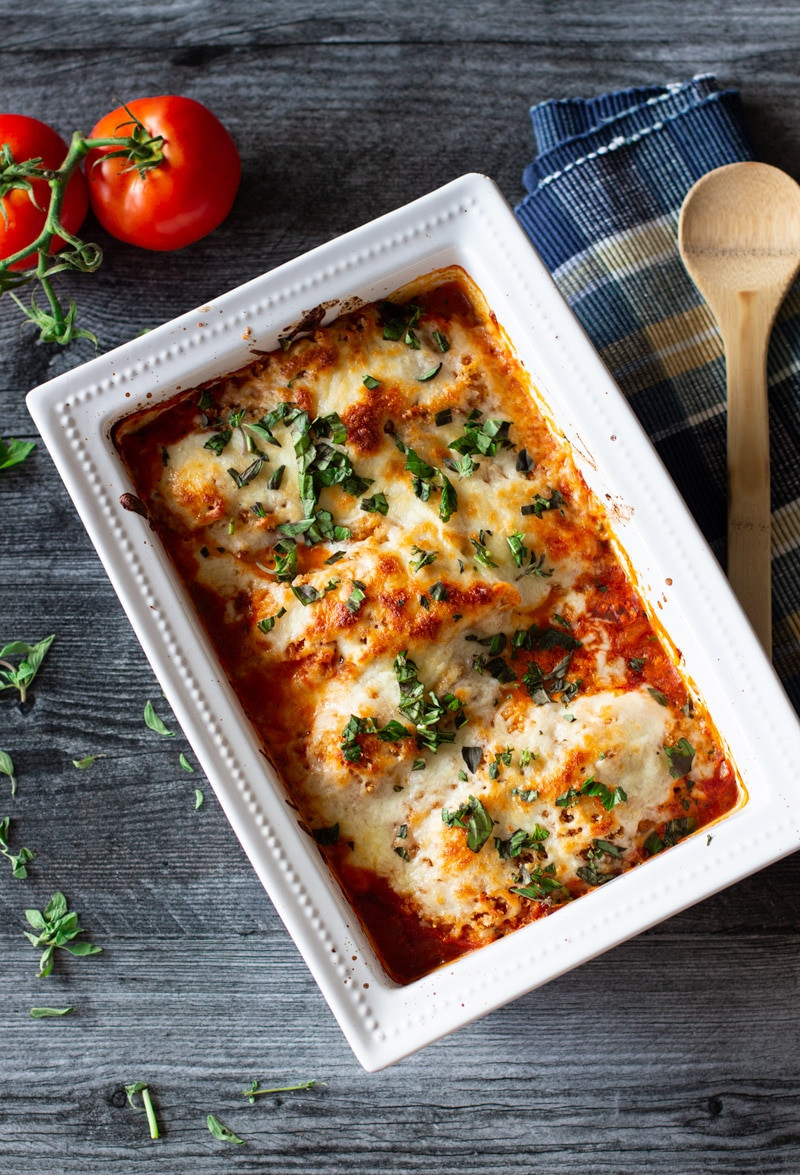 White dish containing chicken topped with melted mozzarella and fresh basil in a pan of marinara sauce.