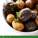 Close up of gemstone smoked potatoes topped with garlic.