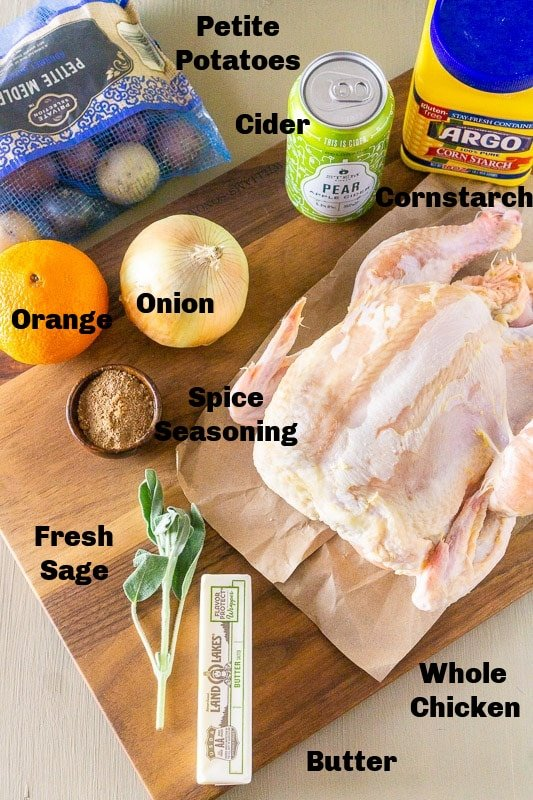 Whole chicken, potatoes, onion, orange, sage, butter, seasonings. hard cider, and cornstarch on a cutting board.
