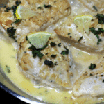 Close up of chicken breasts cooked in a dutch oven topped with cream sauce.