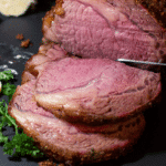 Person slicing a smoked prime rib roast.
