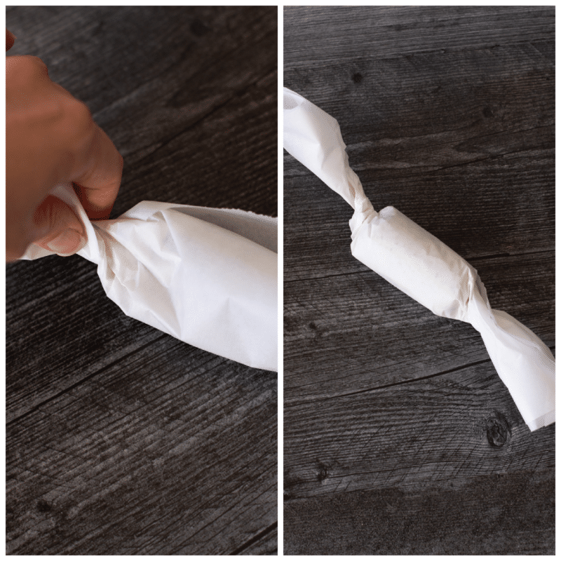 Person rolling compound butter in parchment paper on a table.