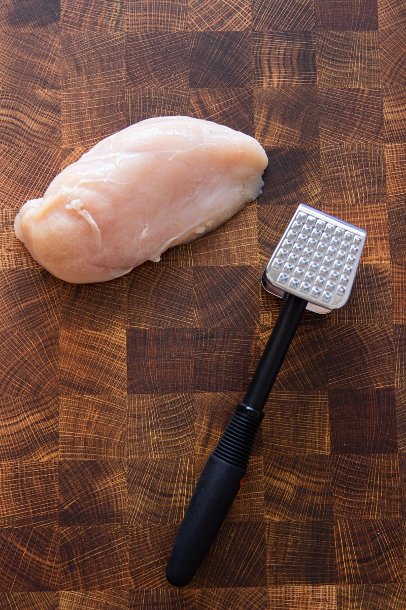 A meat tenderizer next to a chicken breast on a cutting board.