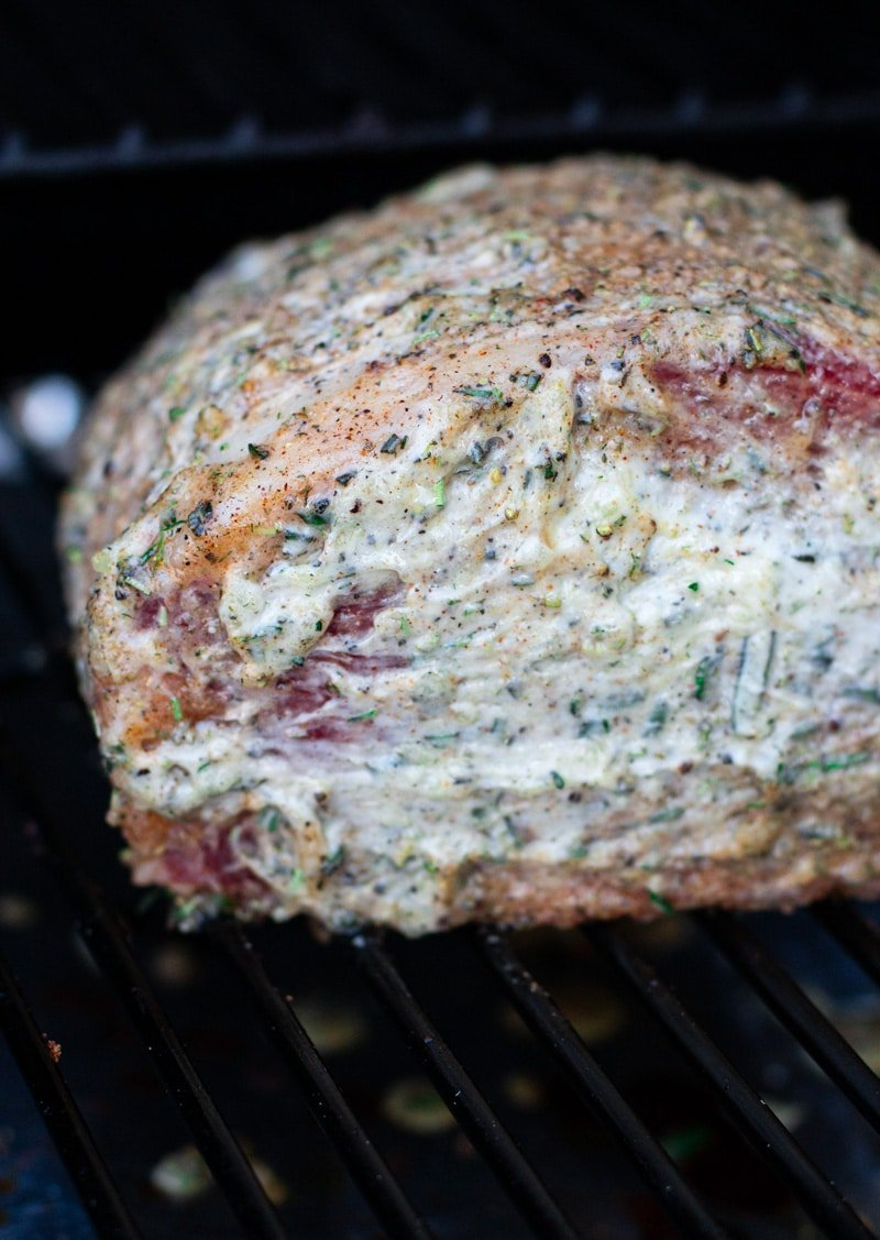 Close up of a prime rib covered in compound butter smoking in a Traeger grill.