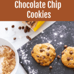 Three chocolate chip cookies on a cutting board.
