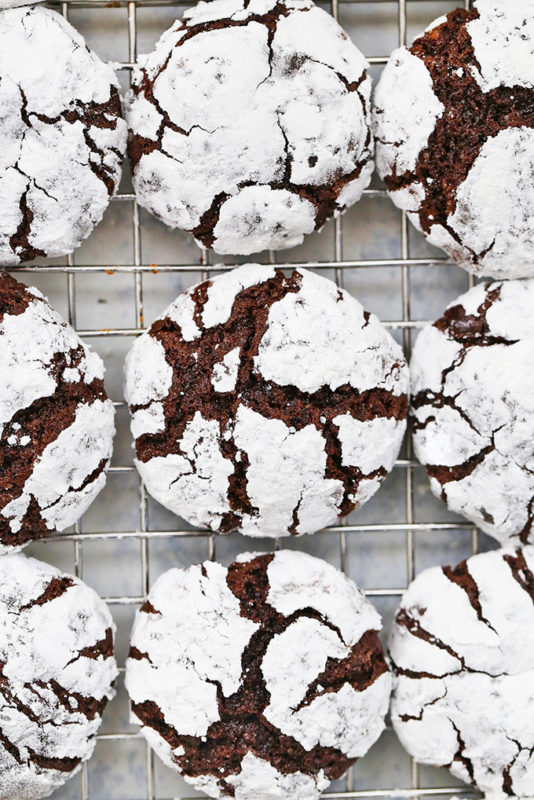 Chocolate and white powdered sugar cookies on a cooling rack.