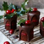 Mini chocolate cakes topped with cranberries, cranberry filling in the middle.