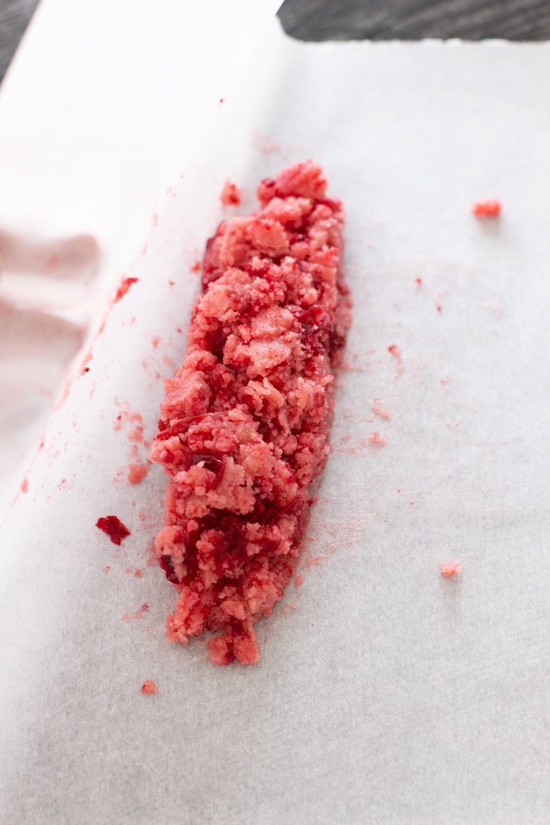 Cranberry butter being wrapped in parchment paper.