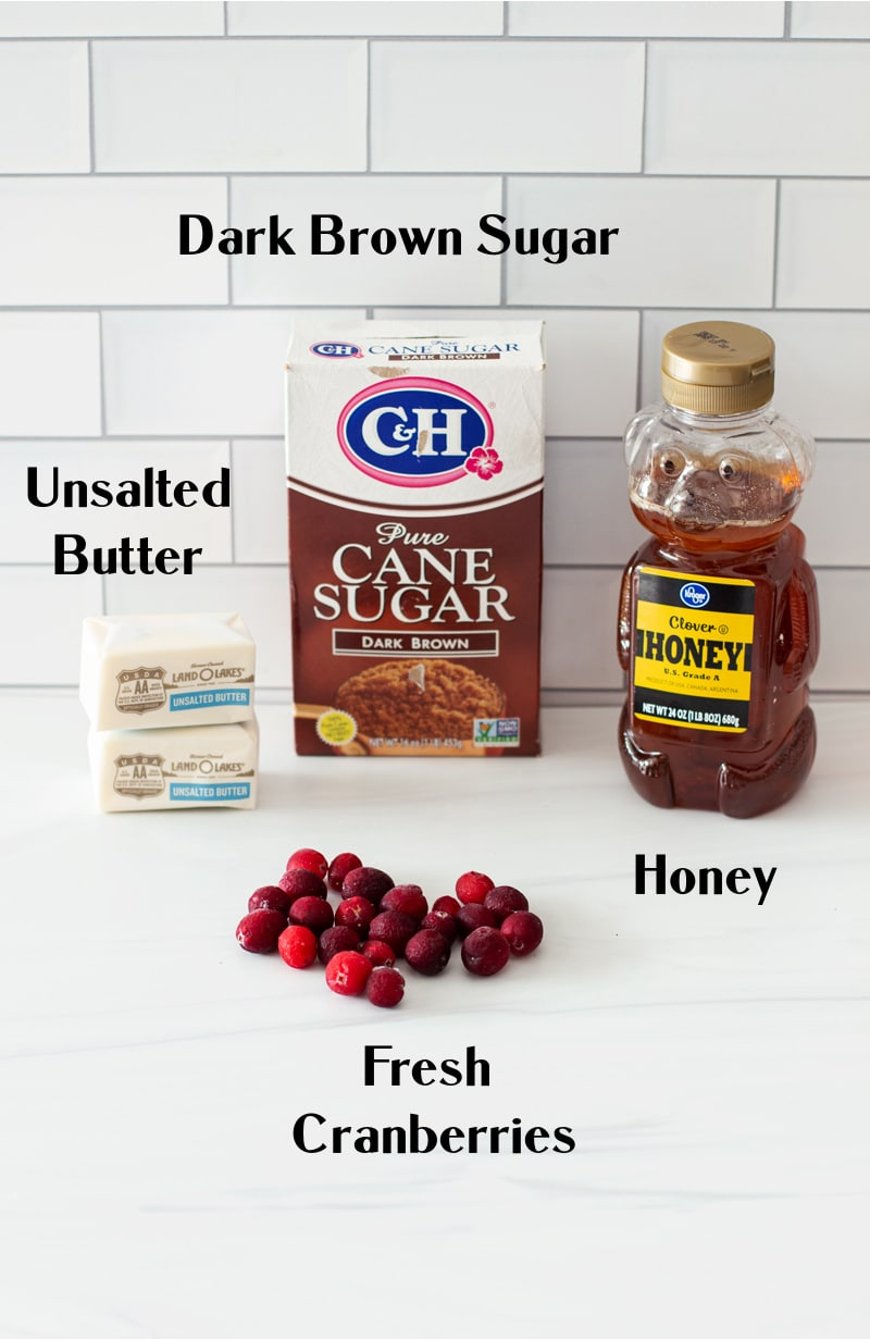 Dark brown sugar, butter, honey, and cranberries on a white counter.