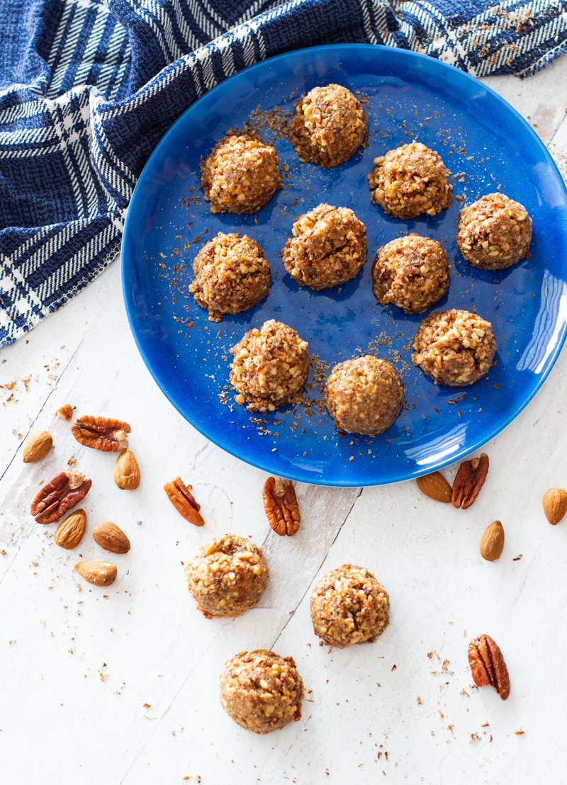10 protein balls on a blue plate nd on counter, mixed nuts on table.