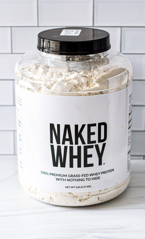 Bin of Naked Whey protein powder on a countertop.