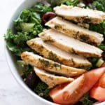 Bowl of greek marinated chicken on a bed of kale salad.