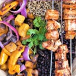 Jackfruit skewers over a bed of rice with vegetables.