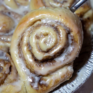 Close up of cinnamon rolls covered in vanilla icing, other cinnamon rolls on platter.