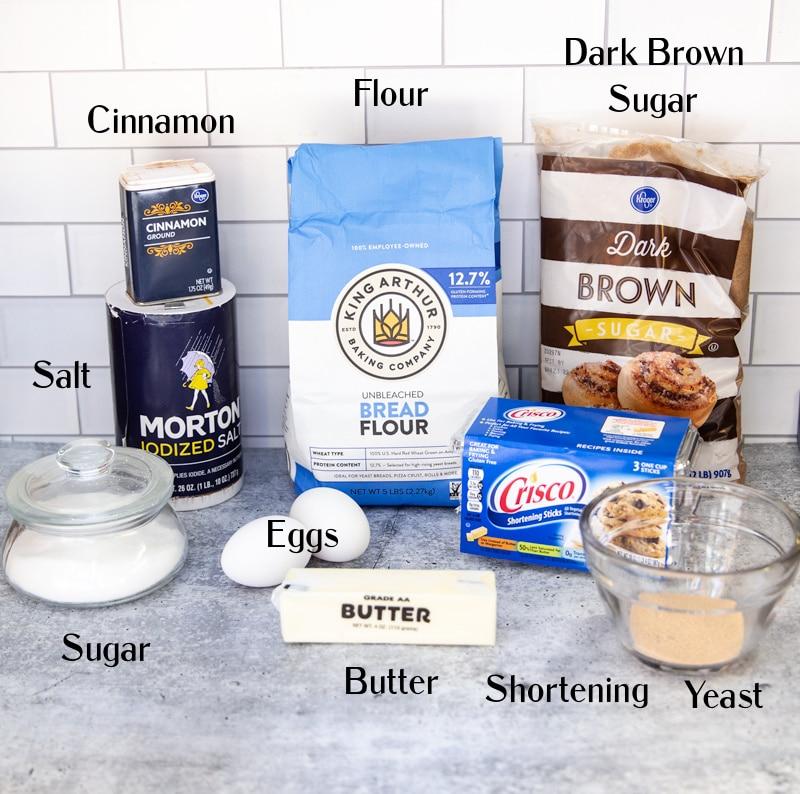 Flour, dark brown sugar, shortening, yeast, butter, eggs, sugar, salt, and cinnamon on counter.
