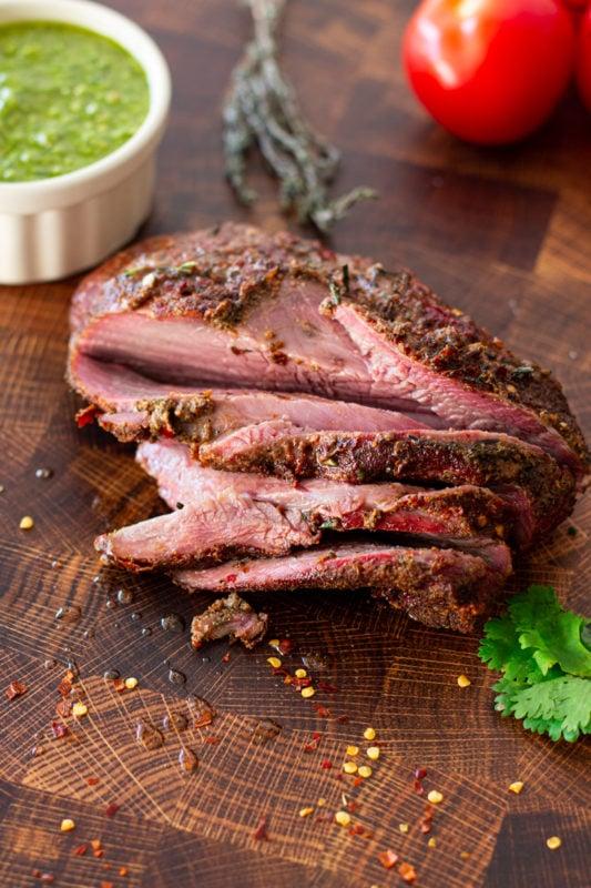 Sliced elk roast on cutting board.