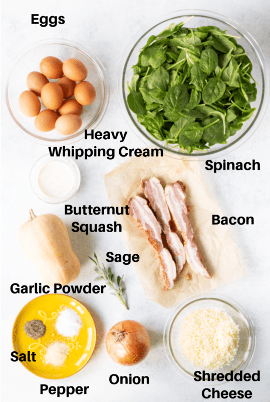 Eggs, spinach, whipping cream, bacon, cheese, and seasonings on a plate.